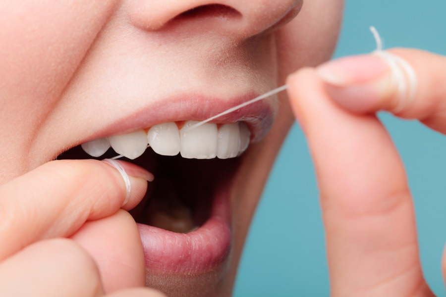 Closeup of a woman using string floss to floss between her teeth