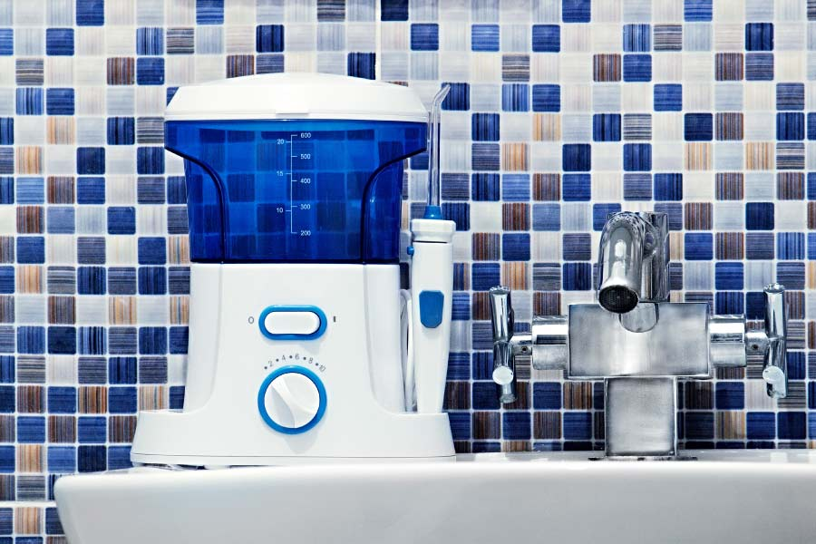 A blue and white water flosser on a bathroom counter against a blue mosaic backsplash