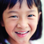 Little girl with dark hair smiles with a healthy smile in San Antonio, TX