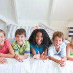 Group of kids on a bed smile with dental sealants in San Antonio, TX
