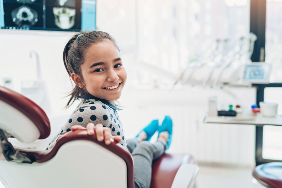 brunette girl smiles while sitting in the dentist chair at Tots to Teens Pediatric Dentistry & Orthodontics in San Antonio, TX