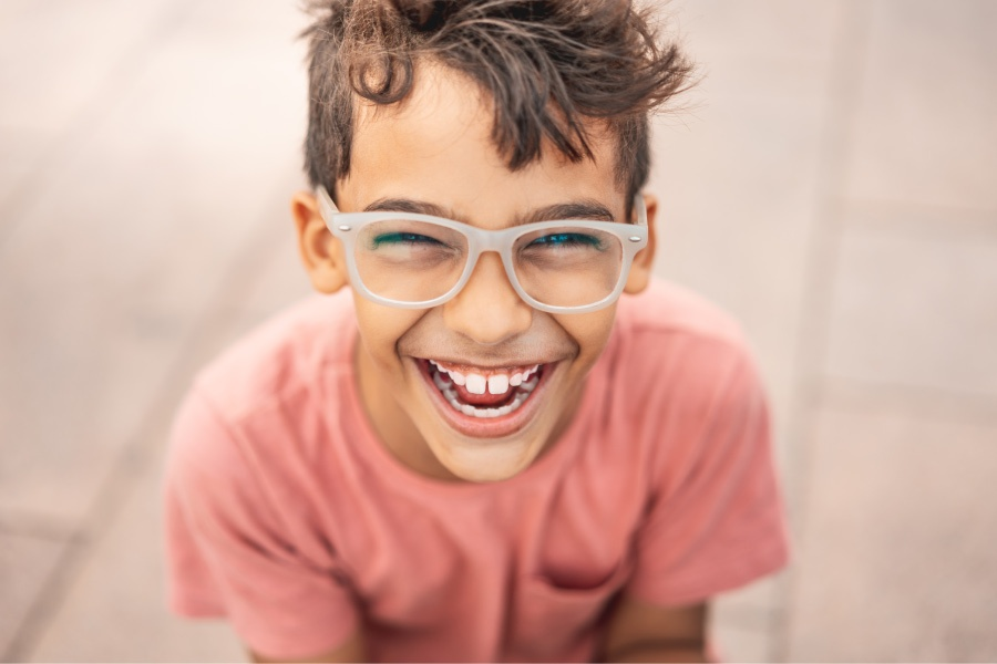 Brunette boy with glasses and dental sealants smile while wearing a salmon-colored shirt