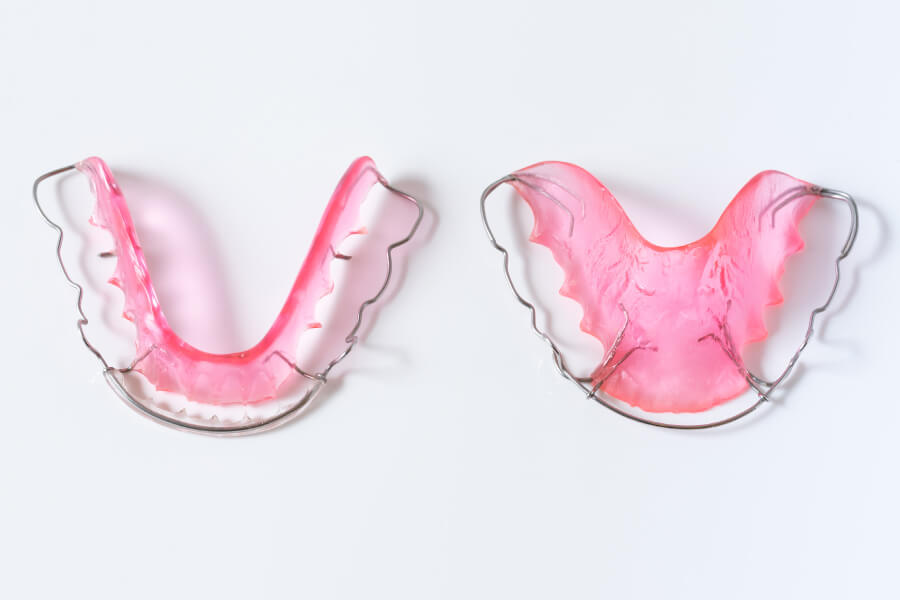 Closeup of a set of pink Hawley retainers worn after orthodontic treatment is finished in San Antonio, TX