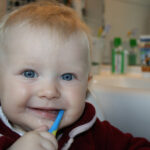 Smiling toddler with a toothbrush in his mouth.