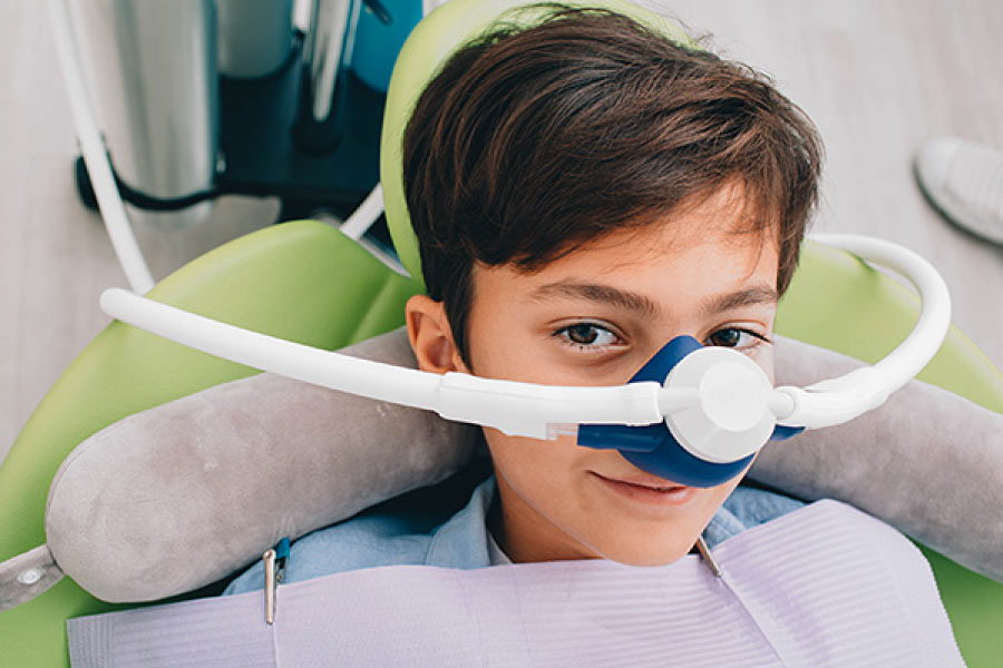 Boy sitting in the dental chair wearing a mask used to dispense nitrous oxide dental sedation.