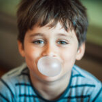 Brunette boy smiles while chewing sugar-free gum and blowing a bubble in San Antonio, TX