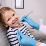 Brunette girl at the dentist smiles in the dental chair before receiving a fluoride treatment